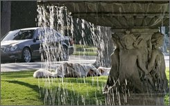  A homeless man sleeps near a fountain in Beverly Hills, Calif., Wednesday, Sept. 10, 2008. The homeless in Beverly Hills present an incongruous sight amid the shows of superfluous wealth, but they've become fixtures of city life, underscoring the pervasiveness of the huge homeless population in Los Angeles County. Some 88,000 people live on the streets or in shelters, making the county the nation's capital of homelessness.  (AP Photo/Reed Saxon)