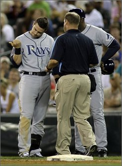 "In this Aug. 7, 2008 file photo, Tampa Bay Rays' Evan Longoria, left, is examined by a trainer after being hit by a pitch thrown by Seattle Mariners closer J.J. Putz in the ninth inning in an MLB baseball game at Safeco Field in Seattle. Longoria was activated off the 15-day disabled list Saturday, Sept. 6, 2008 after the Tampa Bay slugger said he felt ""almost 100 percent"" following 30 swings with a regular bat. (AP Photo/Ted S. Warren, file)"