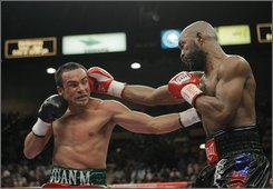 Juan Manuel Marquez, left, of Mexico, takes a punch from Joel Casamayor, of Cuba, in the second round of their 12-round lightweight boxing match in Las Vegas, Saturday, Sept. 13, 2008. (AP Photo/Jae C. Hong)