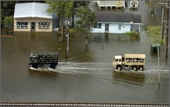 Louisiana National Guard hi-water vehicles carry evacuees out of Erath, La. following the landfall of Hurricane Ike Saturday, Sept. 13, 2008.  (AP Photo/Richard Alan Hannon, Pool)