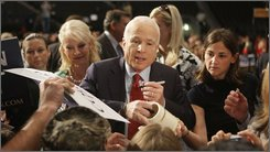 Republican presidential candidate Sen. John McCain, R-Ariz., flanked by his wife Cindy, left, and campaign aide Brooke Buchanan, right, signs autographs for supporters during a campaign rally in Jacksonville, Fla., Monday, Sept. 15, 2008.  (AP Photo/Stephan Savoia)