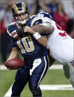 St. Louis Rams quarterback Marc Bulger, left, is sacked for a seven-yard loss by New York Giants defensive tackle Fred Robbins during the second quarter of an NFL football game Sunday, Sept. 14, 2008, in St. Louis. (AP Photo/Tom Gannam)