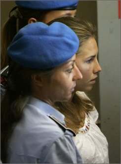 American murder suspect Amanda Knox, at right in white top, is escorted by Italian penitentiary police officers, outside Perugia's court, central Italy, Tuesday Sept. 16, 2008. A judge in Perugia is leading a hearing Tuesday on a request for trial for Knox and two other suspects in the 2007 slaying of British student Meredith Kercher in this university town in Umbria. Suspect Amanda Knox, who is from Seattle, showed up in court, but her former Italian boyfriend Raffaele Sollecito did not. The third suspect, Rudy Hermann Guede, an African who lives in Perugia, was attending the hearing. All three deny wrongdoing. (AP Photo/Antonio Calanni)