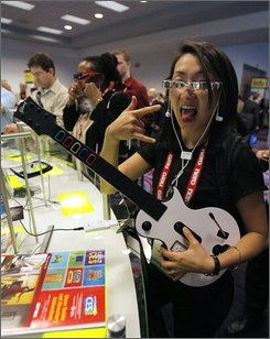 In this Jan. 9, 2008 file photo, Judy Mellett of Toronto poses while playing a video game through Myvu's personal media viewer at the Consumer Electronics Show in Las Vegas. A new national survey from the Pew Internet & American Life Project found that while they don't necessarily play the same thing, nearly all U.S. youth -- girls included -- play video games of one kind or another. (AP Photo/Jae C. Hong, file)