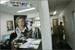 Supporters of Tzipi Livni, Israeli Foreign Minister and candidate for Kadima party leadership, seen on the posters on the wall, work at Livni's headquarters in Netanya, Israel, Tuesday, Sept. 16, 2008.  Israel's popular foreign minister Tzipi Livni squares off against a tough-talking military man Shaul Mofaz on Wednesday when the ruling Kadima Party chooses a new leader to replace Prime Minister Ehud Olmert, who is being forced from office by a corruption scandal. (AP Photo/Ariel Schalit)
