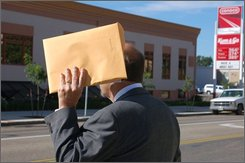 Howard O. Kieffer, who's accused of impersonating a lawyer, hides his face outside the federal courthouse in Bismarck, N.D., on Monday, Sept. 15, 2008.  Kieffer's trial has been scheduled for Nov. 18 in Bismarck. He is charged with mail fraud and making false statements. (AP Photo/James MacPherson).