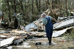 A man walks among hurricane ravage homes in the aftermath of Hurricane Ike  in Oak Island, Texas, Wednesday, Sept. 17, 2008. Oak Island, a  coast community of fishermen and retirees,  was nearly wiped out by Hurricane Ike. (AP Photo/Marcio Jose Sanchez)