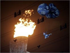 A performer is suspended in the air, near the Paralympic flame, during the closing ceremony of the Paralympic Games at the National Stadium in Beijing Wednesday, Sept. 17, 2008. (AP Photo/Greg Baker)