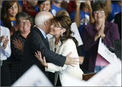 Republican presidential candidate Sen. John McCain, R-Ariz., gets a hug from his vice presidential running mate, Alaska Gov. Sarah Palin, before speaking at a rally, Thursday, Sept. 18, 2008, in Cedar Rapids, Iowa.  (AP Photo/Charlie Neibergall)