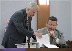 Clark County Deputy District Attorney Chris Owens, left, and Las Vegas police detective Andy Caldwell look at court documents during O.J. Simpson's trial in Las Vegas, Thursday, Sept. 18, 2008. Simpson faces 12 charges, including felony kidnapping, armed robbery and conspiracy. (AP Photo/Steve Marcus, Pool)