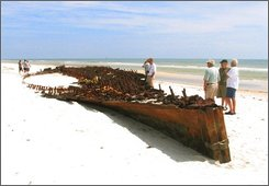 People look over the wreck of a wooden ship uncovered by Hurricane Ike on a beach on Fort Morgan Road in Fort Morgan, Ala., Tuesday, Sept. 16, 2008.  Archeologists say the wreck could be that of a two-masted Civil War schooner that ran aground in 1862 or another ship from some 70 years later. The wreck had already been partially uncovered when Hurricane Camille cleared away sand in 1969. Researchers at the time identified it as the Monticello, a battleship that partially burned when it crashed trying to get past the U.S. Navy and into Mobile Bay during the Civil War. (AP Photo/Press-Register, Guy Busby)