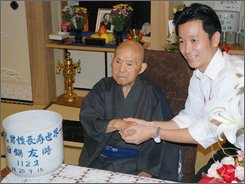 Tomoji Tanabe, left, the world's oldest man is congratulated by Miyakonojo Mayor Makoto Nagamine on his 113th birthday Thursday at his home in Miyakonojo on Japan's southern island of Kyushu Thursday, Sept. 18, 2008. (AP Photo/Kyodo News)