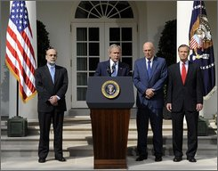 President Bush, second from left, standing with, from left, Federal Reserve Chairman Ben Bernanke, Treasury Secretary Henry Paulson and Securities and Exchange Commission (SEC) Chairman Christopher Cox, makes a statement about the economy and government efforts to remedy the crisis, Friday, Sept. 19, 2008, in the Rose Garden of the White House in Washington. (AP Photo/Susan Walsh)