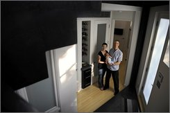 Alice Speck poses with her husband, Jeff Speck, and their infant son, Milo, in Washington on Monday Aug. 25, 2008, framed by the staircase in their new home. The Speck's chose not to build a parking spot into their home, as they do not own a car. (AP Photo/Jacquelyn Martin)