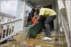 Workers dump debris from a home in Galveston's historic downtown district Friday, Sept. 19, 2008, in Galveston, Texas. The area, which hosts well-known Mardi Gras and Charles Dickens festivals each year, was one of they city's hardest hit areas by flooding from Hurricane Ike.  (AP Photo/Rick Bowmer)