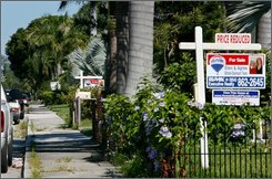 """For sale"" signs line the front yards of several houses in a Hollywood, Fla. neighborhood on Saturday, Sept. 20, 2008. Housing agents say buyers seem more confident now that the federal government is stepping in to stabilize the economy, but potential buyers still face tough challenges qualifying for mortgages. Experts say that the government's enormous plan to relieve Wall Street banks of their bad investments has a decent chance of stabilizing home prices, at least in theory. If that happens, it will stop Wall Street's bleeding, but could still keep many families locked out of the housing market. (AP Photo/Marianne Armshaw)"