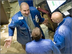 Specialist Peter Giacchi, left, talks with two colleagues on the floor of the New York Stock Exchange, Friday, Sept. 19, 2008. Wall Street extended a huge rally Friday as investors stormed back into the market, relieved that the government plans to restore calm to the financial system by rescuing banks from billions of dollars in bad debt. (AP Photo/Richard Drew)