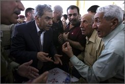 In this July 15, 2008 file photo, Iraqi lawmaker, Mithal al-Alousi, 2nd left, talks with internally displaced persons in Baghdad, Iraq. Iraqi legislators say parliament has voted to lift the immunity of a Sunni Arab lawmaker Mithal al-Alousi who visited Israel.  The parliament has also banned  al-Alousi from traveling outside Iraq or attending parliamentary sessions. (AP Photo/Hadi Mizban)