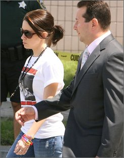 Casey Anthony, left, walks with her attorney Jose Baez on Monday, Sept. 15, 2008 at the Orange County Jail just before surrendering his client on newly-filed charges in Orlando, Fla. The mother of a missing toddler, who authorities have called a person of interest in the girl's disappearance, was arrested a third time Monday on new theft charges.  (AP Photo/Orlando Sentinel, Red Huber)