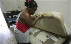 "Marcia Escalona cleans up her room at a temporary government-provided shelter in Havana, Monday, Sept. 15, 2008.  About 450,000 homes were damaged, more than 63,000 of them beyond repair, after hurricanes Gustav and Ike struck the island eight days apart in late August and early September. At least 200,000 Cubans were left newly homeless and the government says ""hundreds of thousands more"" may have to find temporary housing. (AP Photo/Fernando Llano)"