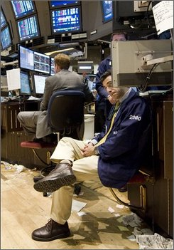 Specialist Peter Mazza, seated at right, looks at the numbers near the close of trading on the floor of the New York Stock Exchange, Monday Sept. 22, 2008. Wall Street tumbled again, sending the Dow Jones industrials down more than 370 points as volatility swept across the financial markets. Investors struggled throughout the day with their anxiety about the government's plan to buy $700 billion in banks' mortgage debt. (AP Photo/Richard Drew)