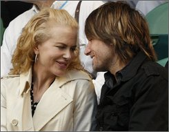 "In this Jan. 21, 2008 file photo, Nicole Kidman and her husband Keith Urban are seen in the stands at the Australian Open tennis tournament in Melbourne, Australia. The Oscar-winning Kidman said swimming in Australian Outback ""fertility waters"" during production of her latest film may have contributed to her unexpected pregnancy. (AP Photo/Rick Stevens, FILE)"