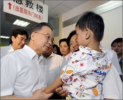 In this photo released by the official Xinhua news agency, Chinese Premier Wen Jiabao, left, calls on a child sickened by tainted milk powder at Beijing Children's Hospital in Beijing on Sunday September 21, 2008. The Chinese leader on Sunday visited hospitals, communities and supermarkets in Beijing to see for himself the infants sickened by tainted milk powder and the milk market, Xinhua said. (AP Photo/Xinhua, Rao Aimin)