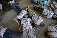Demonstrators lay outside the entry to the capitol building housing the state parole board, in protest of the scheduled execution of Troy Davis, on Tuesday Sept. 23, 2008, in Atlanta. Davis was convicted of the 1989 murder of an off-duty police officer, however seven of the nine witnesses who helped put Davis on death row have since recanted their testimony. (AP Photo/John Amis)
