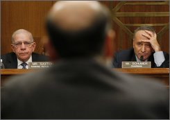 Joint Economic Committee Chairman Sen. Charles Schumer, D-N.Y., right, and the committee's Ranking Republican, Rep. Jim Saxton, R-N.J., left, listen as Federal Reserve Chairman Ben Bernanke, back to camera, testifies before the committee, Wednesday, Sept. 24, 2008, on Capitol  Hill in Washington. (AP Photo/Charles Dharapak)
