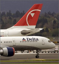 In this April 23, 2008 file photo, a Delta plane taxis for takeoff past a Northwest plane at Portland International Airport in Portland, Ore. Delta and Northwest shareholders are expected to vote Thursday Sept. 25, 2008 on combining to create world's biggest carrier.  (AP Photo/Don Ryan, file)