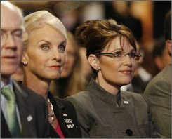 Republican vice presidential candidate Sarah Palin, right, and Cindy McCain, wife of Republican presidential candidate, Sen. John McCain, R-Ariz.,listen to McCain speak at the Clinton Global Initiative in New York, Thursday, Sept. 25, 2008. (AP Photo/Gerald Herbert)