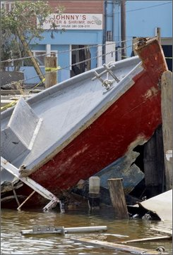 A damaged fishing boat is shown near Johnny's Oyster & Shrimp, Inc. in the aftermath of Hurricane Ike Wednesday, Sept. 24, 2008 in San Leon, Texas. On the eve of October's peak harvesting season, migrant fishermen are sweeping debris from gutted bay side homes instead of scooping seafood from the lucrative Gulf floor, and a $100 million fishing industry in Galveston Bay is virtually paralyzed. (AP Photo/David J. Phillip)