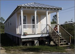 Donnell Landtroop sits on the steps of her state-supplied Mississippi cottage that was damaged by Hurricane Gustav and has been condemned in Bay St. Louis, Miss. Tuesday, Sept. 23, 2008. The Mississippi Emergency Management Agency has condemned more than 230 of the cottages, leaving Landtroop and other coastal Mississippi residents scrambling to find shelter in a storm-scarred region where affordable housing is scarce. (AP Photo/Alex Brandon)