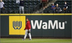  Los Angeles Angels' Juan Rivera walks by a Washington Mutual advertisement in right field during batting practice before a baseball game against the Seattle Mariners at Safeco Field  in Seattle, Thursday, Sept. 25, 2008. JPMorgan Chase &amp; Co. has struck a deal to acquire the deposits and some of the branches of beleagured thrift Washington Mutual Inc., according to news reports late Thursday.  (AP Photo/John Froschauer)