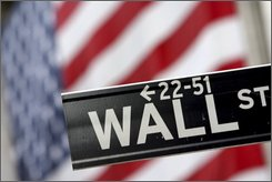The Wall St. street sign is photographed in front of the American flag hanging on the New York Stock Exchange prior to a NYC Central Labor Council rally for worker protections, Thursday, Sept. 25, 2008 in New York.  (AP Photo/Mary Altaffer)