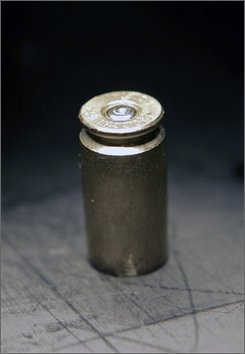 In this file photo taken May 19, 2008, a shell casing is placed under a microscope to identify markings left on it after being fired from a handgun during a demonstration at the New York State Police headquarters in Albany, N.Y.  Since March 2001, identifying information about more than 200,000 new pistols and revolvers sold in New York have been entered into the Combined Ballistic Identification System database maintained by state police. New guns are test fired and the minute markings the guns make on the shell casings are recorded and entered into the digital database.  (AP Photo/Mike Groll, file)
