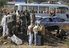 Lebanese residents, background, look at the remains of a booby-trapped car that was parked on a roadside and exploded near a bus transporting Lebanese soldiers in the northern city of Tripoli, Lebanon, Monday, Sept. 29, 2008. A car bomb exploded near a military bus carrying troops heading to their work in northern Lebanon Monday, killing at least five people and wounding 21, Lebanese security officials said. (AP Photo)