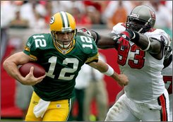 Green Bay Packers quarterback Aaron Rodgers (12) is chased from the pocket by Tampa Bay Buccaneers' Kevin Carter (93) during the first quarter of an NFL football game, Sunday Sept. 28, 2008 in Tampa, Fla. (AP Photo/Reinhold Matay)