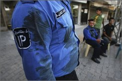 An Iraqi police officer stands at the site of a deadly bombing in central Baghdad's district of Karrada, Monday, Sept. 29, 2008. A parked car bomb exploded at a commercial complex as people were shopping shortly after sundown Sunday and minutes later a suicide bomber set off a second explosion as onlookers and security forces gathered near the first blast, police said. At least 22 people were killed in the blasts. (AP Photo/Hadi Mizban)