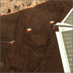 This photo released by NASA shows the edge of a solar panel on NASA's Phoenix Mars Lander, right, in a trench on the surface of Mars, where a sample of soil was taken by the lander. NASA announced Monday, Sept. 29, 2008, that the spacecraft discovered two minerals in the Martian soil that suggest interaction with water in the past. (AP Photo/NASA, JPL-Caltech)