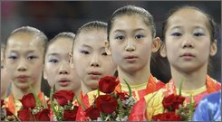 In this Aug. 13, 2008 file photo, members of China's gymnastics team, from left, Yang Yilin, Li Shanshan, He Kexin, Jiang Yuyuan and Deng Linlin listen to their national anthem after winning the gold medal in the women's team final competition at the Beijing 2008 Olympics  in Beijing.  The investigation into the ages of China's gold-medal women's gymnastics team has been expanded to include members of the 2000 team that won a bronze in Sydney, The Associated Press has learned.  Questions about the ages of the Chinese gymnasts at the 2008 Summer Olympics had swirled for months before the games. The International Gymnastics Federation at the IOC's urging, asked China three days before the games ended to provide more information on the ages of five of the six team members