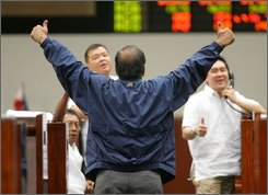 Traders gesture as they react during trading at the Philippines Stock Exchange Thursday, Oct. 2, 2008 in Manila's financial district of Makati. The market jumped 43.2 points, or 1.7 percent, to 2612.89, as investors bet on U.S. lawmakers approval of a $700-billion bailout plan. (AP Photo/Pat Roque)