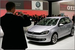 A visitor takes a snapshot of the new Volkswagen Golf VI after its unveiling during the first press day at the Paris Auto Show, Thursday, Oct. 2, 2008. The show runs through Oct. 4 - 19. (AP Photo/Remy de la Mauviniere)