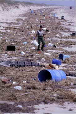  A National Park ranger walks through debris at the Padre Island National Seashore at South Padre Island, Texas, Tuesday, Sept. 30, 2008. Debris from Hurricane Ike that was washed from the Bolivar Peninsula and Galveston litters more than 60 miles of the national seashore. (AP Photo/Eric Gay)