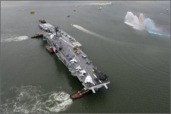 The World War II aircraft carrier Intrepid is moved via tugboat up the Hudson river to it's berth, Thursday, Oct. 2, 2008. The Intrepid Sea Air & Space Museum occupied the Manhattan space until late 2006, when it was moved for extensive repairs and improvements costing nearly US$120 million.  (AP Photo/Mary Altaffer)