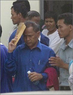 Khem Ngun, center, a former Khmer Rouge soldier, is escorted by police out of the Phnom Penh Municipal Court Phnom Penh, Cambodia, Friday, Oct. 3, 2008. Five former Khmer Rouge soldiers went on trial Friday for their alleged involvement in the killing of a British mine-clearing expert and his Cambodian colleague 12 years ago. (AP Photo/Heng Sinith)
