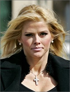 Anna Nicole Smith, leaves the U.S. Supreme Court, in this Feb. 28, 2006, file photo in Washington. A judge ordered a Texas doctor and his wife on Friday, Oct. 3, 2008 not to distribute videotaped footage of Anna Nicole Smith's breast augmentation surgery in 1994. (AP Photo/Manuel Balce Ceneta,File)