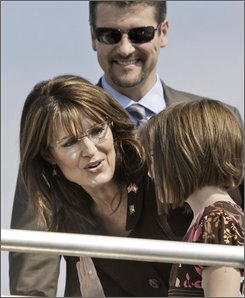 Republican vice presidential candidate, Alaska Gov. Sarah Palin, center, talks with her daughter Piper and her husband, Todd Palin before boarding the campaign plane to leave Dallas, Friday, Oct. 3, 2008.  (AP Photo/LM Otero)
