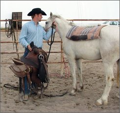 Horse trainer Bryan Mantle of Wheatland, Wyo., saddles  mustang Snowflake on his girlfriend's parents ranch in Bayard, Neb.,  Aug.  8 , 2008. It took Mantle three days of training before he could saddle Snowflake and seven days before he could ride him. (AP Photo/Matt Joyce)