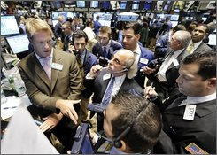 Specialist Patrick Murphy, left, directs trades in Citicorp at the closing bell, on the floor of the New York Stock Exchange, Friday  Oct. 3, 2008. Stocks ended a volatile week with another sell-off Friday while credit markets remained strained after enthusiasm over the government's $700 billion financial rescue plan gave way to worries about obstacles still facing the economy.  (AP Photo/Richard Drew)